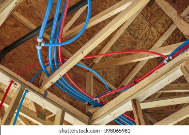 New Home Construction with PEX Plumbing pipes and exposed beams.
