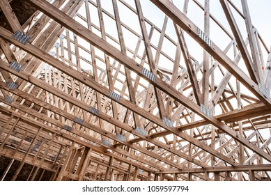 New home construction work site, interior looking up at roof trusses constructed of wood lumber 2x4's