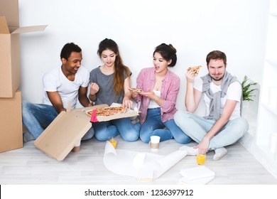 New home. Friends sitting on the floor in the new apartment and eating pizza after unpacking. Housewarming.