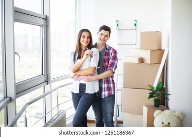 New Home. Funny young couple enjoy and celebrating moving to new home. Happy couple at empty room of new home.