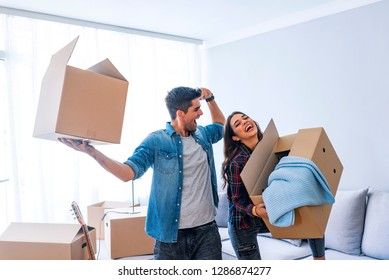 New Home. Funny young couple enjoy and celebrating moving to new home. Happy couple at empty room of new home. Happy couple is having fun with cardboard boxes in new house at moving day.