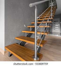 New home interior in grey with simple wooden staircase with steel railing