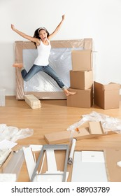 New home - moving woman excited and happy jumping of joy with moving boxes. Young Asian Caucasian woman.