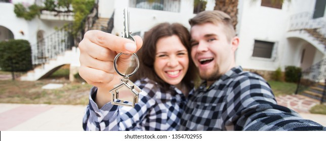 New Home, real estate and moving concept - Funny young couple showings keys from new house.