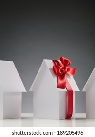 New home - a row of white paper houses one of which is wrapped with a red ribbon.