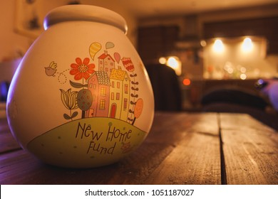 New Home Savings Fund pot sat on a wooden table in a warm comfy house.