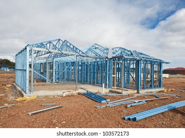 New home under construction using steel frames against cloudy sky