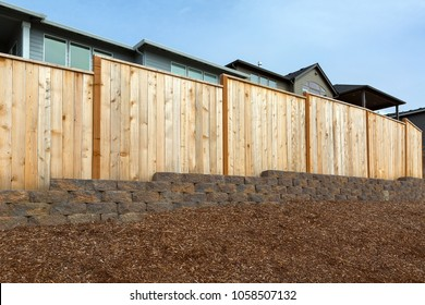 New homes backyard wood fence stone wall and landscaping garden barkdust mulch