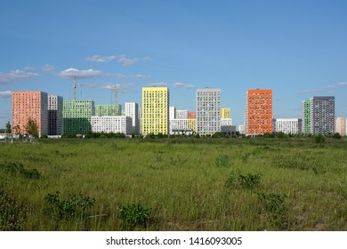 New homes, young city in a green field against a blue sky.
