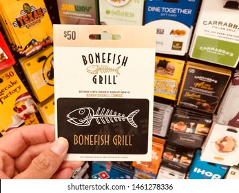 New Hope, Minnesota - July 24, 2019: Hand holds up a Bonefish Grill gift card for sale at a retail store. This is an American casual seafood restaurant chain