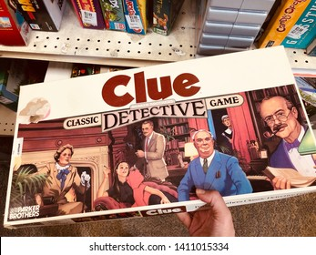 New Hope, Minnesota - May 26, 2019: Hand holds a classic, vintage Clue Detective board game, from the 1990s. Made by Parker Brothers