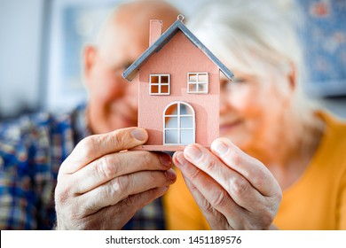 New house concept, happy senior couple holding small home model