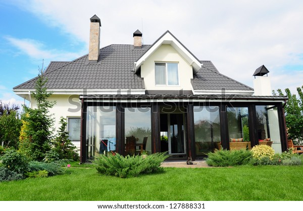 A new house with a garden in a rural area under beautiful sky