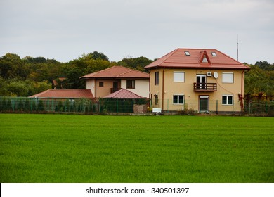 A new house with green grass field in front and forest in the background