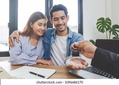 new house / home moving and relocation concept. Happy asian couple receiving apartment key from real estate agent / realtor.