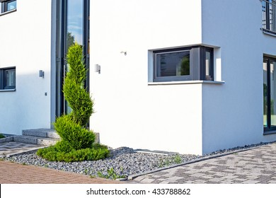 New house with white wall, small windows and green spiral cypress, Germany