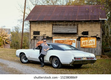 NEW IBERIA, L.A. / USA - NOVEMBER 30, 2014: CCpixx photographer, Crystal Champagne, stand by a 1969 Buick Riviera holding a black cat.