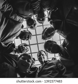 NEW IBERIA, L.A. / USA - OCTOBER 10, 2015: A group of men standing in a circle looking down toward the camera. Camera lookin up toward their faces from the ground.