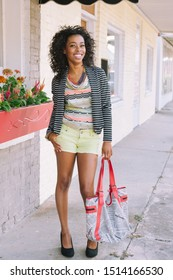 NEW IBERIA, L.A. / USA - SEPTEMBER 10, 2012: Portrait of cheerful young black woman walking down the street wearing fun, sassy bright colored clothing in South Louisiana.