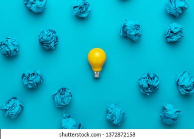 new idea concept with crumpled office paper and light bulb. top view of great business idea concept over blue background. creative solution during brainstorming session concept