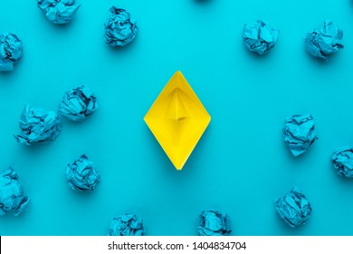 new idea concept with crumpled office paper and yellow paper ship. top view of great business idea concept over blue background with yellow paper boat in the center