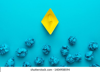 new idea concept with crumpled office paper and yellow paper ship. top view of great business idea concept over blue background. moving forward concept with yellow paper boat as a creative idea