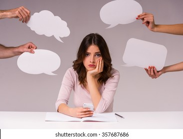 The new idea. Girl sits at a table at the head of the new ideas in the form of empty bubble for text, isolated on a gray background