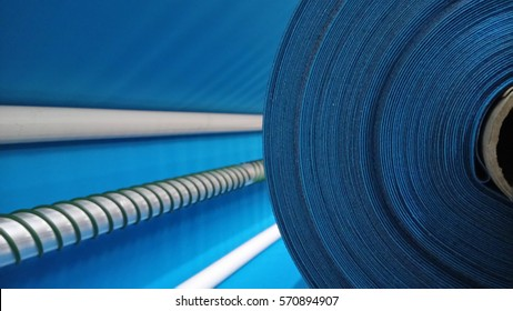 New industrial blue roll, blue background. Concept: material, fabric, manufacture, garment factory, new samples of fabrics.