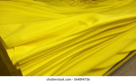 New industrial yellow roll, yellow background. Concept: material, fabric, manufacture, garment factory, new samples of fabrics.