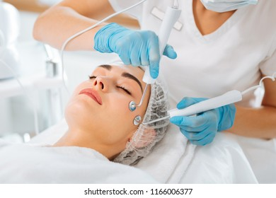 New innovations. Beautiful young woman trying microcurrent therapy while visiting a beauty salon