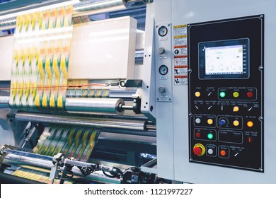 new innovative technology of automatic label printing machine with the digital control panel is printing on continuous plastic film for wrapping on food product packaging in the printing factory.