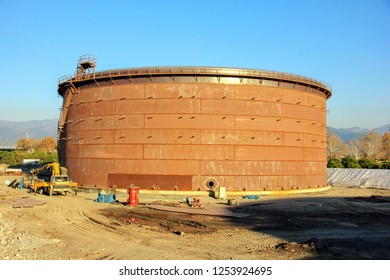 New installation crude oil storage tank with floating roof and a crane in the construction site. Storage tanks are containers that hold liquids, compressed gases or mediums used for the short.