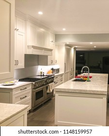 new interior home renovation of modern white kitchen design with upper glass cabinets, base doors and drawers, kitchen island with granite or marble or quartz counter top, undermount sink and faucet