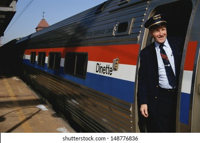 NEW JERSEY - CIRCA 1990's: Conductor squinting from doorway of dinette car in New Jersey