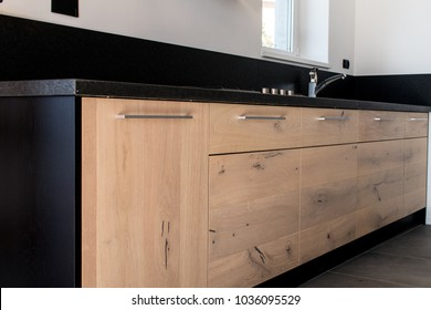 New kitchen in oak and black granite and stainless steel with island, sink, doors, shelves and extractor hood. Industrial design cuisine in a renovated apartment with gray concrete floor. Oak  wood