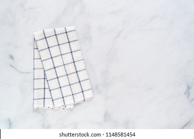 New kitchen towels with simple blue pattern folded on marble counter.
