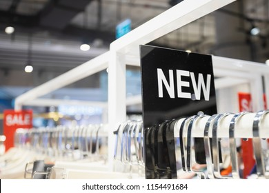 NEW label on clothes rack in the woman clothing shop.