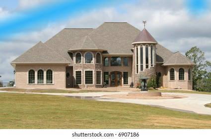new large home on a hill built of rock blue skies in the background