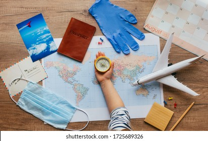New life after Pandemic COVID-19 concept. Planning Travels and Tourism after the End of Quarantine. Kids hand holding retro compass near map, face mask, medical gloves, passport, calendar.