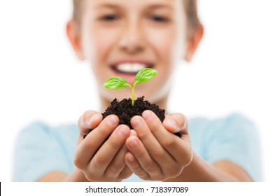 New life concept - handsome smiling child boy hand holding small green plant sprout leaf growth at dirt soil heap white isolated