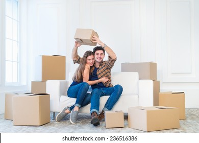 New life in a new home. Couple in love enjoys a new apartment and keep the box in his hands while young and beautiful couple in love sitting on the couch in an empty apartment among boxes.