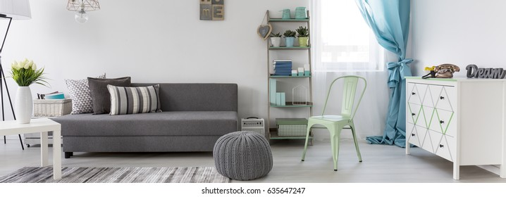 New living room in scandinavian style with grey sofa and white commode, panorama