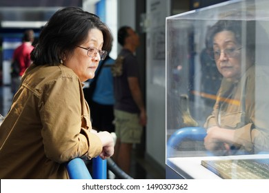 New London, CT / USA - June 22, 2019: Middle-aged Asian female visitor observes an exhibit at the Submarine Force Museum