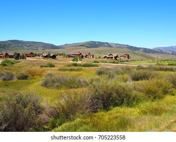 New luxurious wood homes on a prairie in Colorado with gentle rolling hills in the background.