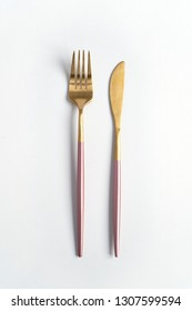 New luxury Golden cutlery view from above on a isolated white background. Top view. Pink knife and fork for a festive table for a wedding, birthday or party.