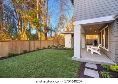 New luxury home with fully fenced back yard with gresh new grass, white furniture and covered deck.