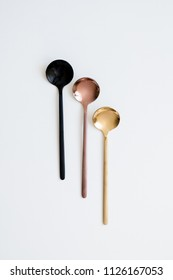 New luxury spoons of gold, copper and black. On white isolated background. Cutlery.