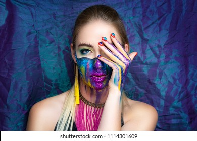 New make-up universe is painted on womans face. Forehead brows eyes are chic evening make-up green color, wavy line divides the face into two parts. At the bottom of her face are streams vivid paint