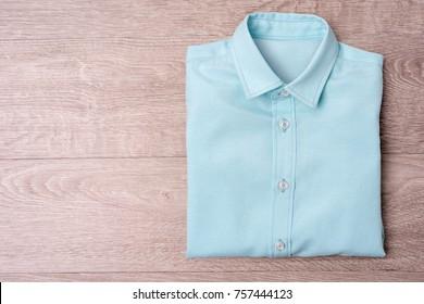 New man's blue shirt  on wood background