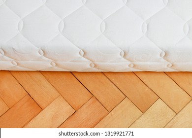 The new mattress and wooden floor. Concept of brand new home.